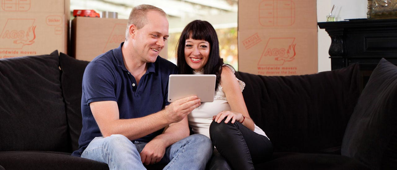 Couple with tablet smiling and sitting on a couch with removal boxes on the back